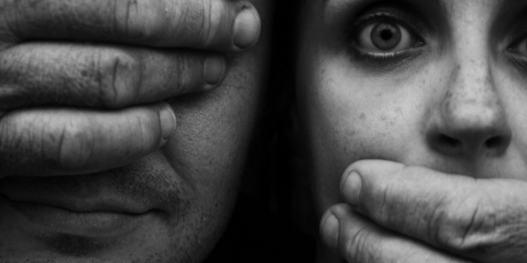 Photo d'un couple dont l'homme se masque les yeux d'une main et baillonne sa femme de l'autre